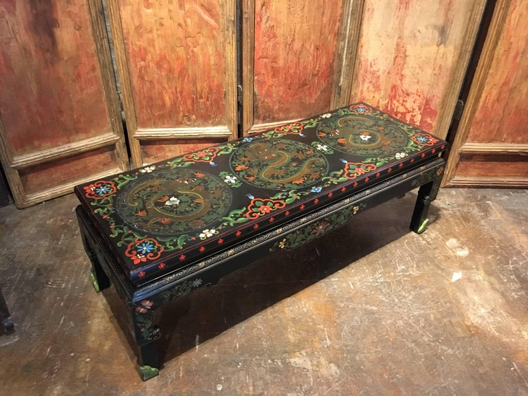 A fun Chinese export Hollywood Regency black lacquer and polychromed coffee table featuring painted roundels of coiled and writhing dragons against a scrolling floral and foliate ground.