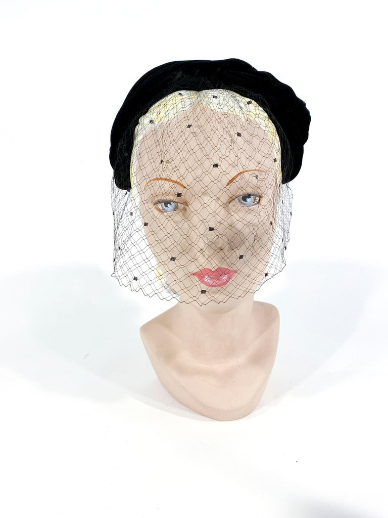 1950s black Christian Dior Black velvet and silk hat fashioned in a modified turban shilouette. The base of the hat has hand-gathering and a center band of black silk. The full-face silk veil is made of silk net.