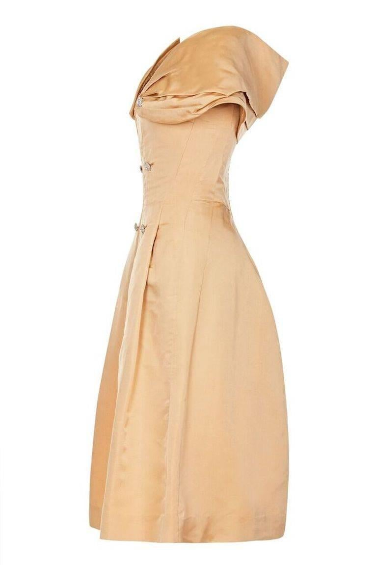 This arresting Christian Dior new York 1950s silk evening dress showcases some incredibly skillful construction and exudes timeless glamour. The fabric is luxurious textured silk in pale gold and has been artfully tailored to create the designer's