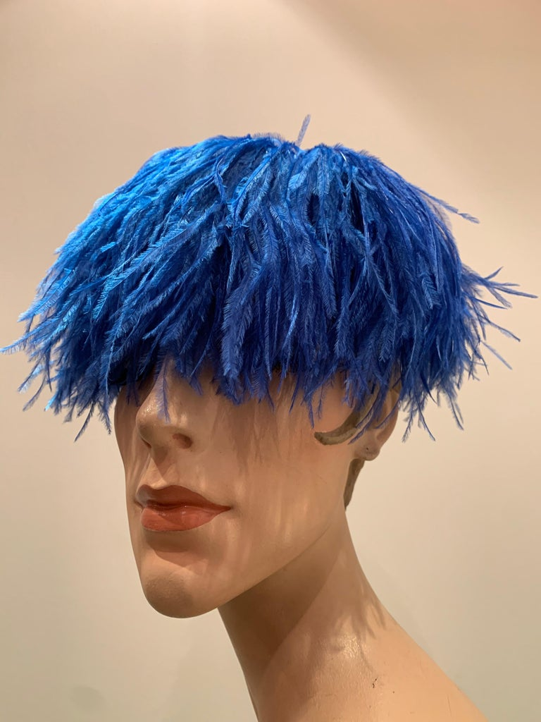 A fabulous 1950s-early 1960s pill box hat from The Woodward Shops covered entirely with lush cobalt blue ostrich feathers with a button-like swirl at center top. Base constructed of stiffened tulle.