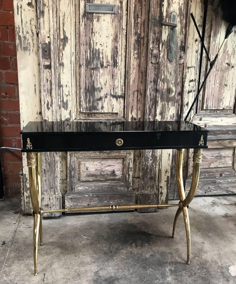 A midcentury Italian console table with black finish and dark black mirrored glass top.