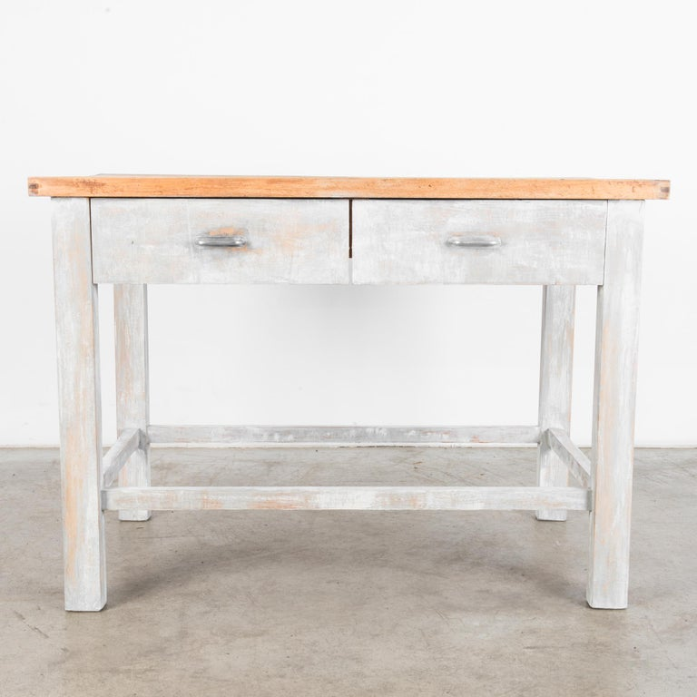 A wood patinated table from Czechia, produced, circa 1950. A sturdy table with a thick tabletop and two drawers straight from a mid-century workshop. A muted palette and unencumbered design allow this piece to function in most any environment.