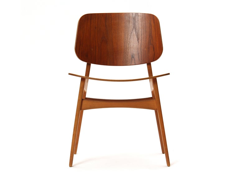 A side chair with a solid beech frame and a seat and back of molded teak plywood. Most bear makers mark.