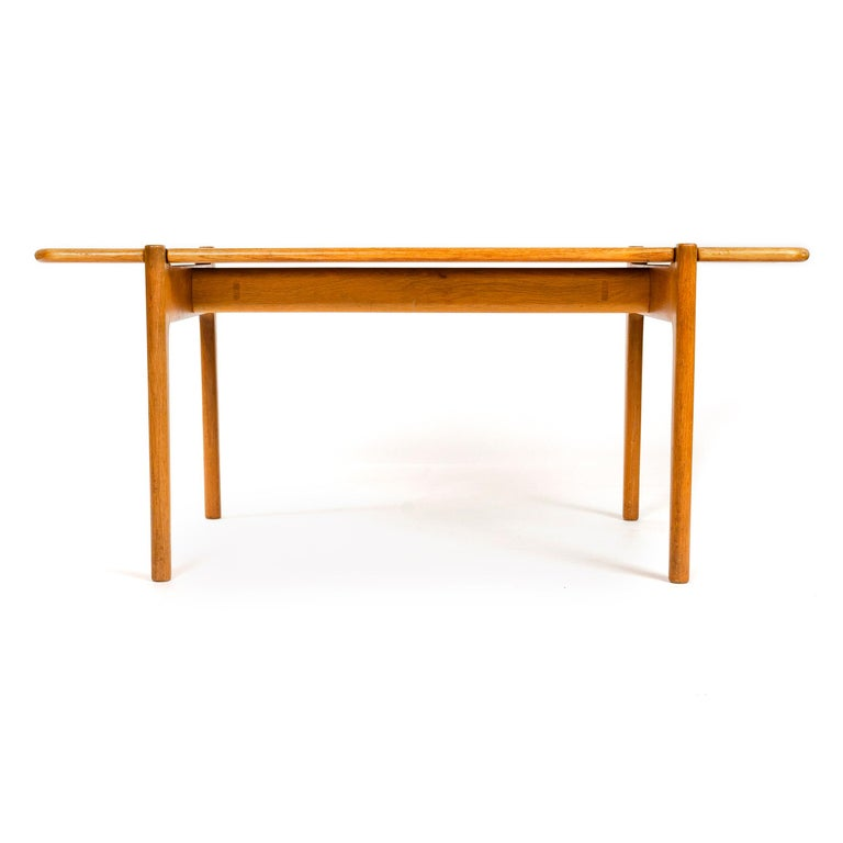 A medium height table with a reversible, shaped edge, rectangular top of solid teak set on a solid oak base. This unit is a custom, unmarked variation from production models 562 and 564 varying in width (shorter), depth (deeper), and height