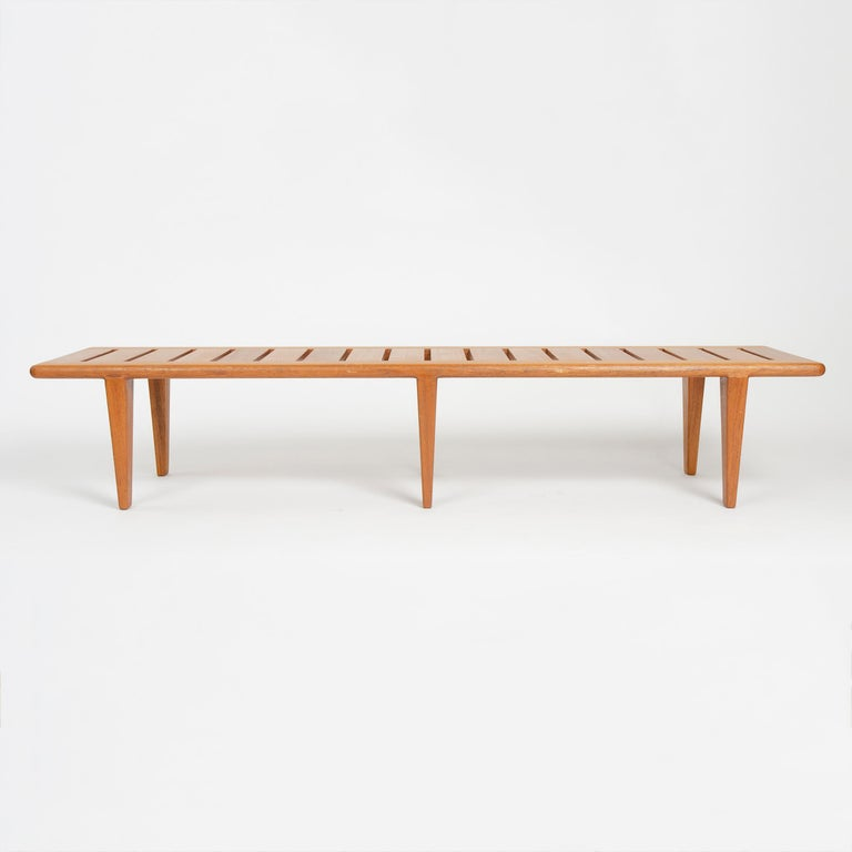 A solid teak bench with a slatted seat over six (6) tapered legs.