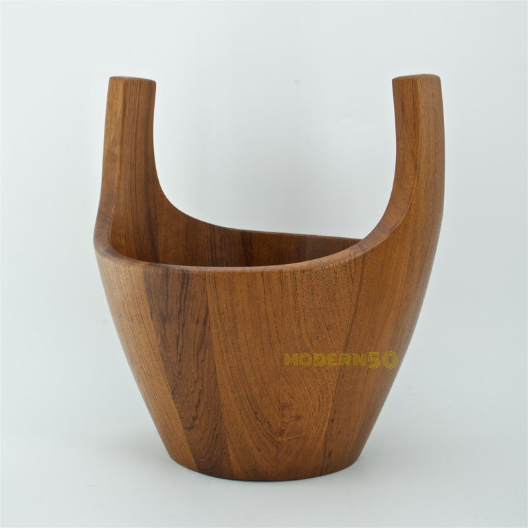 Denmark, circa 1950s. Staved teak bowl designed by Jens Quistgaard for Dansk. A midcentury re-interpretation of the traditional wooden Quaich. Measures: 10 5/8 inches high, 10 inches wide, 9 1/2 inches deep. Branded mark on underside, three duck