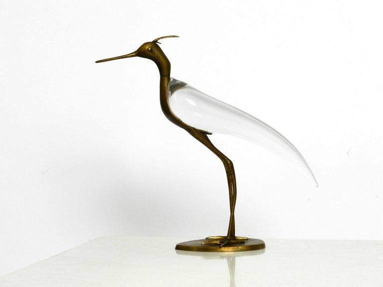 Very beautiful decorative mid century modern heron made of solid brass and with a torso made of clear glass. Designed by Luca Bojola for Licio Zanetti. Florence Italy. Very high quality with many details. With beautiful patina on the brass. The
