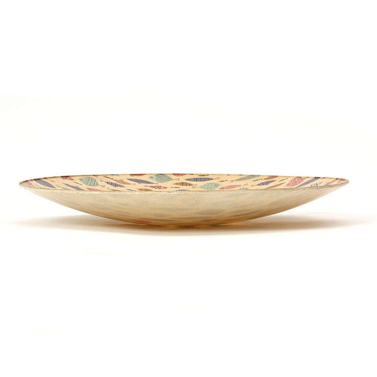 A low fiberglass bowl with repeating images of multicolored fish.