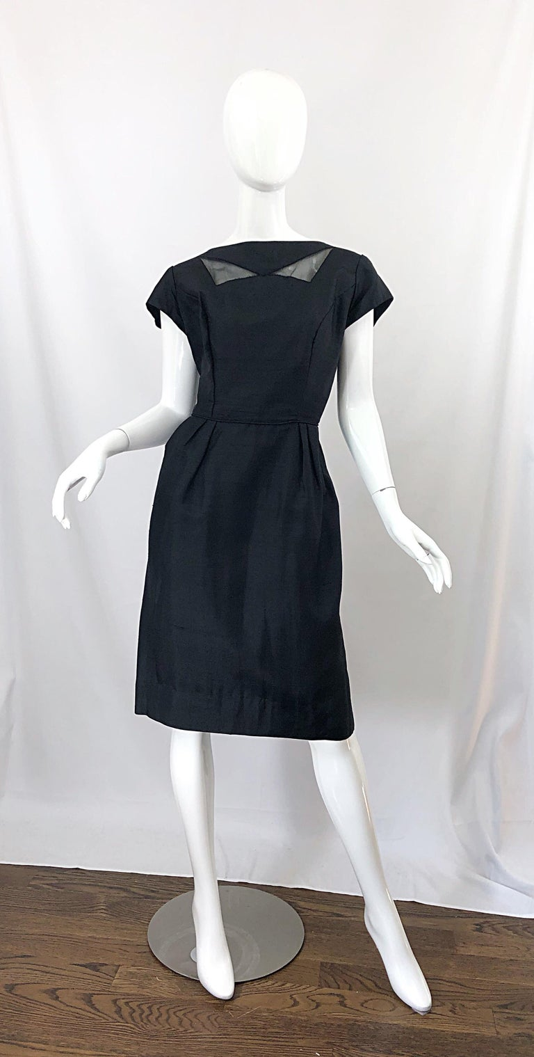 Chic 1950s demi couture black silk cut-out cocktail dress! Features a fitted bodice and forgiving skirt. Low cut back features a large bow that snaps on one side. Full metal zipper up the back with hook-and-eye closure. Cut outs at the top neck