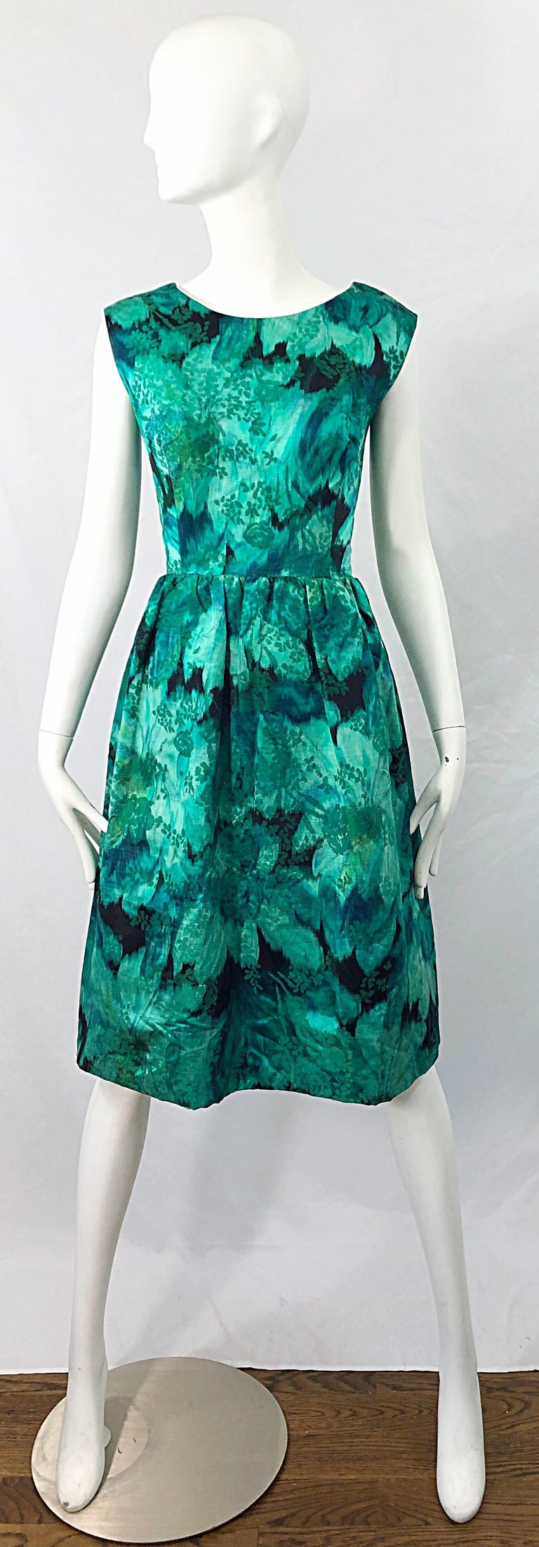 Beautiful 1950s demi couture green botanical floral print silk fit n' flare sleeveless dress ! Features various shade of green throughout. Hidden metal zipper up the back with hook-and-eye closure. Can easily be worn for any day or evening event.