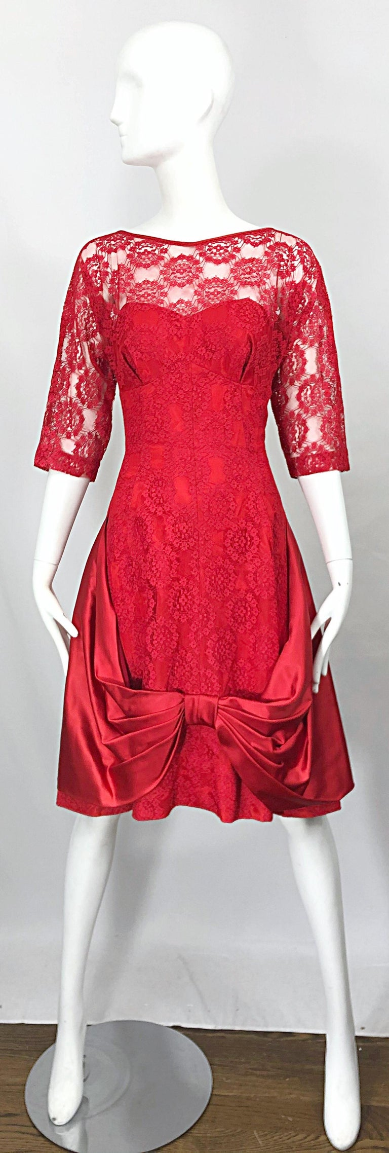Incredible 1950s demi couture lipstick red silk lace fit n' flare cocktail dress! Features silk taffeta with red lace overlay. Large satin bow detail at center front hem. Fitted tailored bodice with a forgiving full skirt. Hidden metal zipper up the
