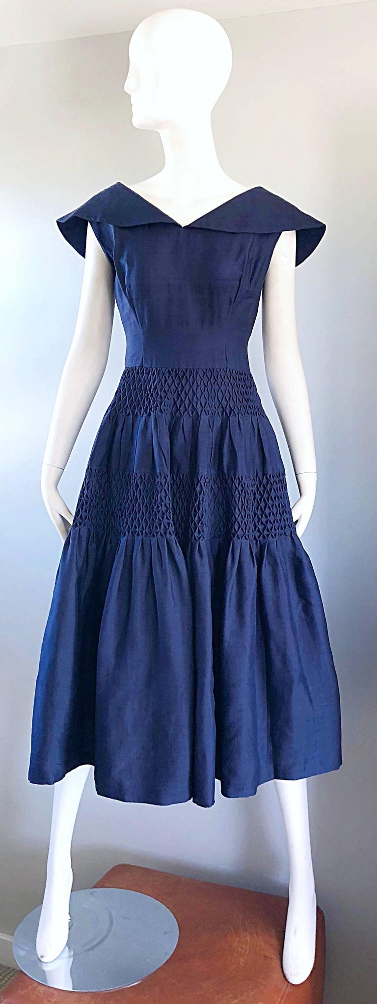 Gorgeous 1950s demi couture navy blue silk shantung nautical fit n' flare dress! Masterfully designed, with a very heavy attention to detail. Fitted bodice, with a forgiving and flattering full skirt. Shawl like collar, with ribbon bow detail on the
