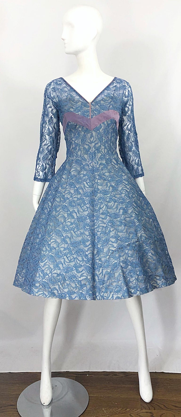 Beautiful 1950s demi couture periwinkle blue fit n' flare chantily lace dress! Features a fitted bodice with a forgiving full skirt. Satin lining at bust, with matching ribbon detail on back. Attached inner slip, with hidden metal zipper up the back