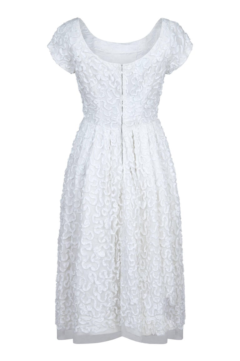 A beautiful and timeless original 1950s pure white tulle ribbon appliqué work dress from high-end British boutique label Diana Warren.  Classic scoop neck, cap sleeves, a fitted bodice and pleating to the waist, the dress is adorned all over in