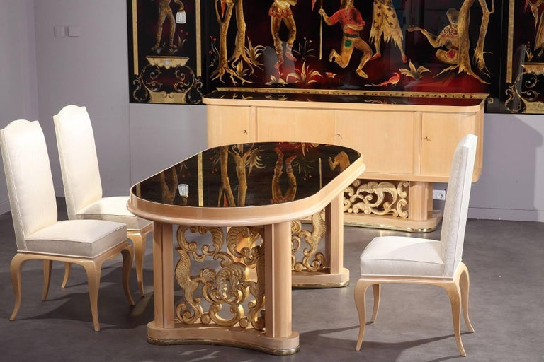 Dining room set in sycamore and sycamore veneer composed of a table, four chairs, two armchairs and a sideboard.  The table with oval tray is set on two curved gilded legs, decorated with birds and foliated scrolls. The chairs and armchairs are