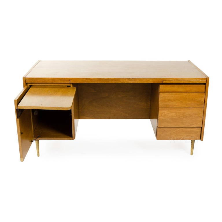 An elegant and finely proportioned bleached walnut double pedestal desk with ample storage floating on dowel-shaped brass legs.
