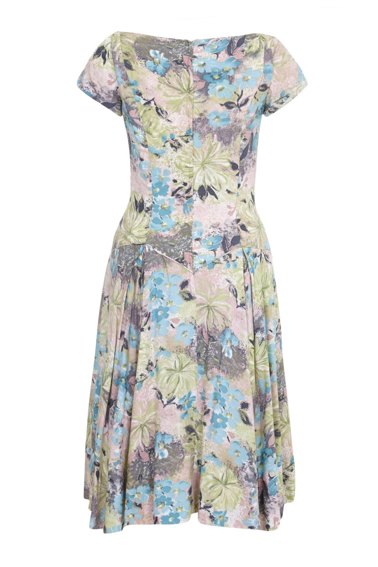 This charming 1950s cotton sun dress with a softly abstracted floral print in soft pastel shades in pink, blue, green and grey is a lovely piece for summer. It features a dropped waist with piping and V shaping to the front and back. There are