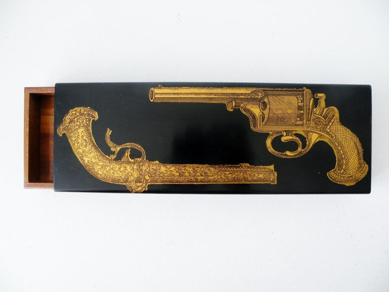 An early enameled metal and mahogany trinket dresser box designed by Piero Fornasetti depicting a pair of pistols. Dates to the late 1950s and made in Italy.