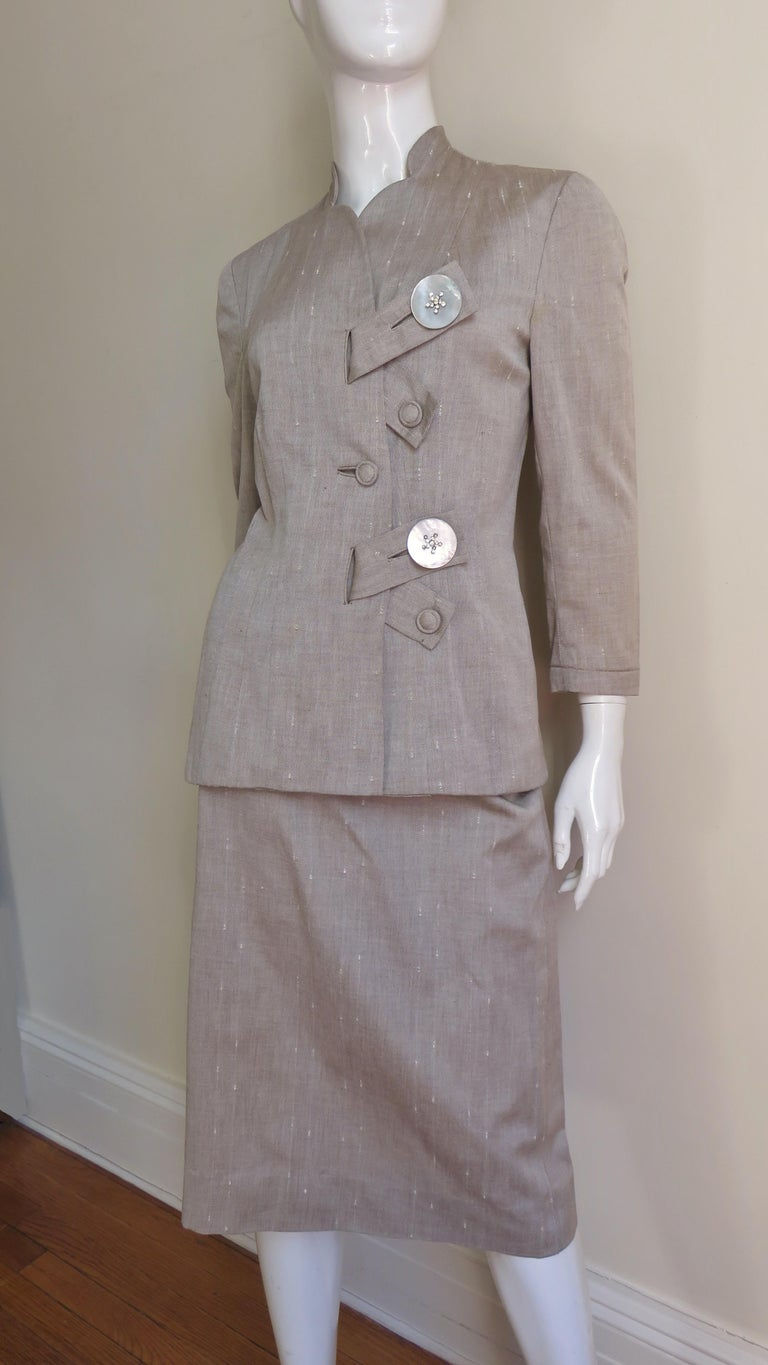 A fabulous suit from Eisenberg Originals in taupe linen cotton blend.  It has 3/4 length sleeves and a unique front closing via diagonal tabs through large bound vertical buttonholes and large gorgeous mother of pearl buttons and smaller self