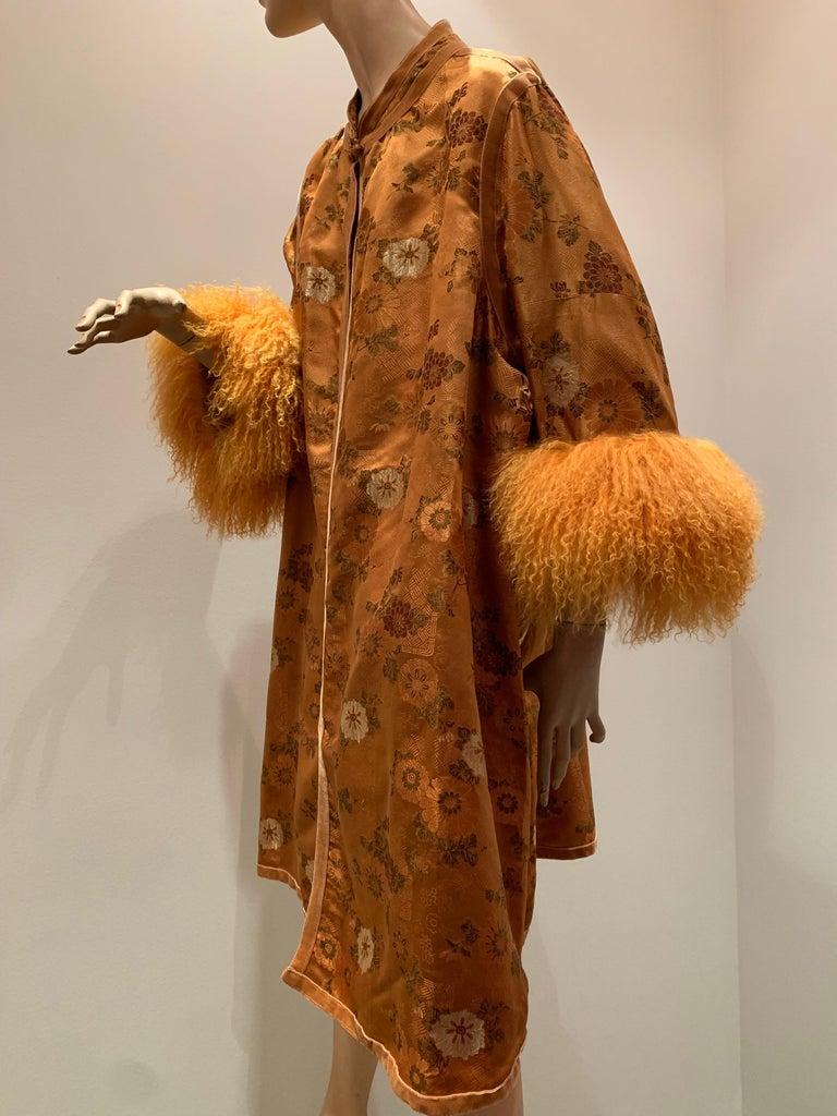 1950s Eleanora Garnett Asian-Inspired Silk Brocade Opera Coat W/ Mongolian Cuffs in Butterscotch. Unlined. Frog closure at neck. Trimmed with velvet ribbon. Mandarin collar.