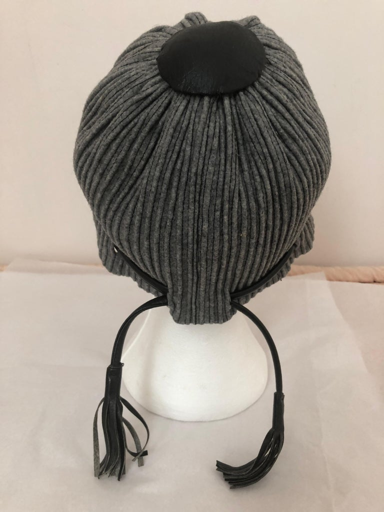 This is a very unique hat from Elsa Schiaparelli, both in style and material. It is made of grey  wool stitched raised ribbing, and black leather lacing ending in tassels. It also has a black leather disc at the top, with gros grain patch on the