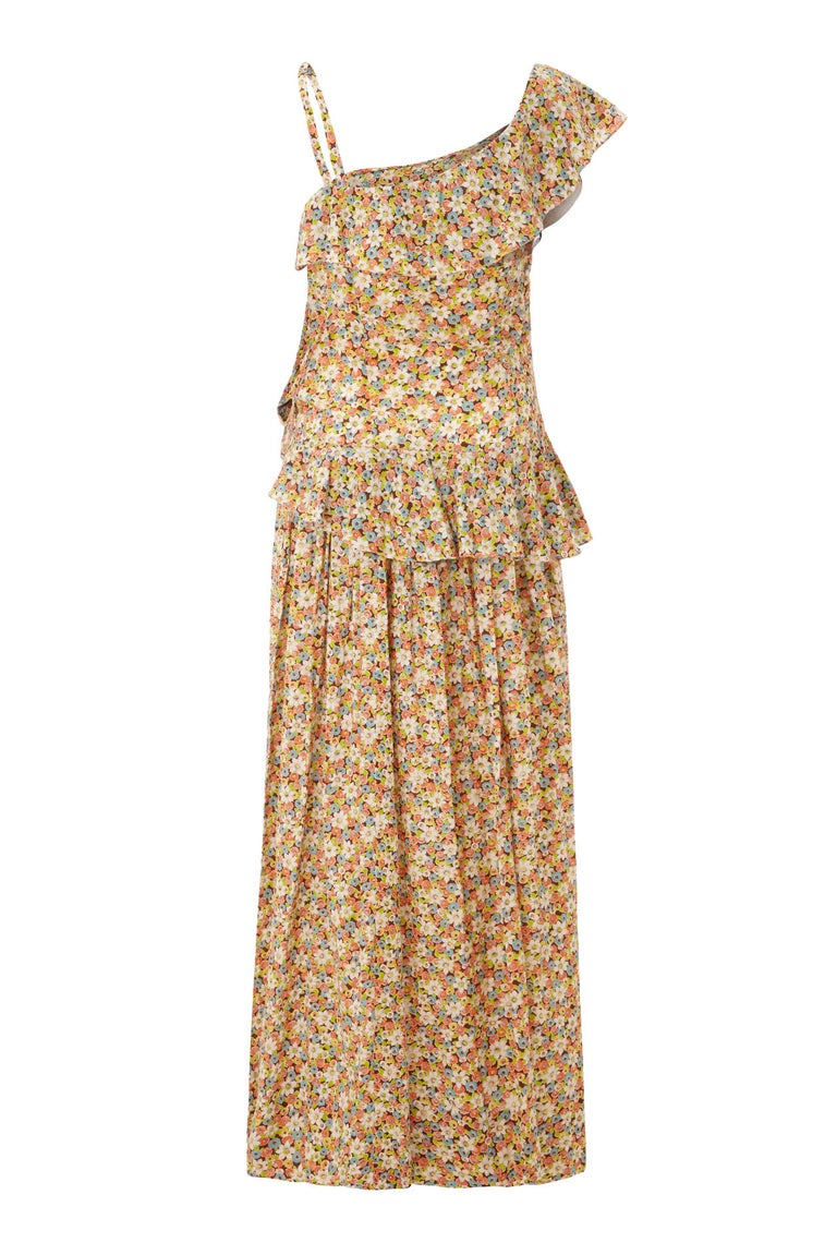 This lovely late 1940s/1950s cotton floral dress from Elysian is in beautiful vintage condition and has a summery floral print in cream, orange, blue, green and brown. The dress features a striking asymmetrical neckline with a single strap