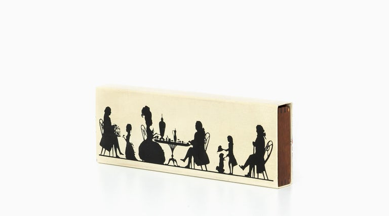 Wonderful and extraordinary vintage Fornasetti box. It has an enameled metal cover with Fornasetti's iconic graphics, showing people silhouette in black and beige. The inner compartment is in wood. The bottom is shiny red felt. Manufactured by