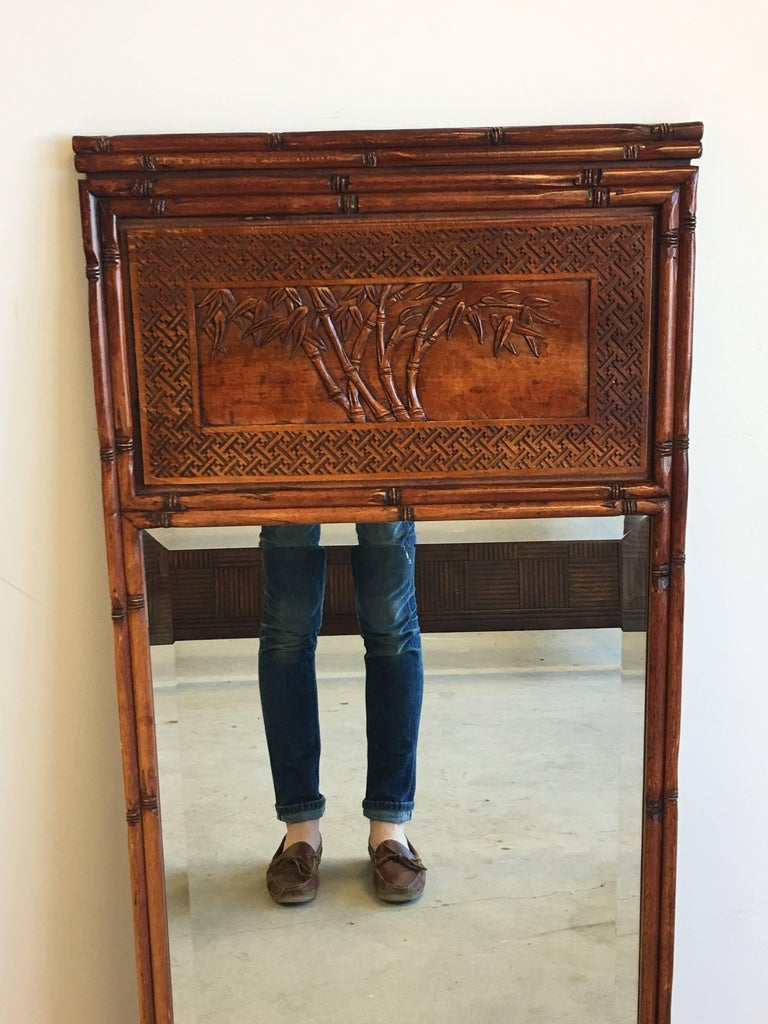 Offered is a beautiful, 1950s faux bamboo mirror. The piece features a faux bamboo border all around, with a Chinoiserie and Greek key detailed trumeau along the top. Beveled mirror.