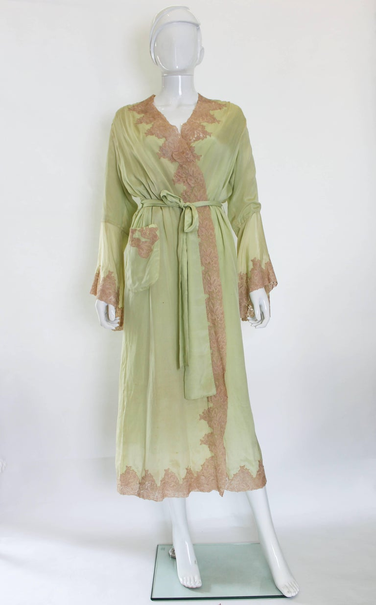 A stunning full length negligee in pistachio green silk, with biscuit coloured lace trim. The negligee is fully lined in silk, so it hangs beautilfuly. There is in internal tie belt and a 4 inch wide belt around the gown. The lace trim is around the
