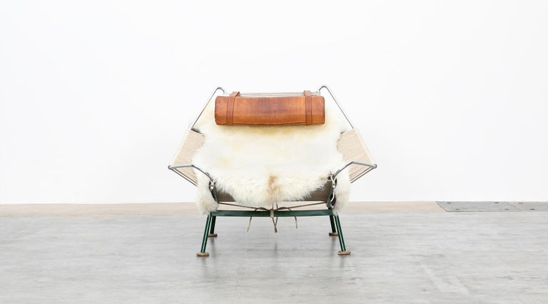 Flag halyard lounge chair, green lacquered metal, leather by Hans Wegner, Denmark, 1950.  The flag halyard chair has a green lacquered base so that it is visible as a supporting part. The seat shell with flag cord resting on it remained unpainted,