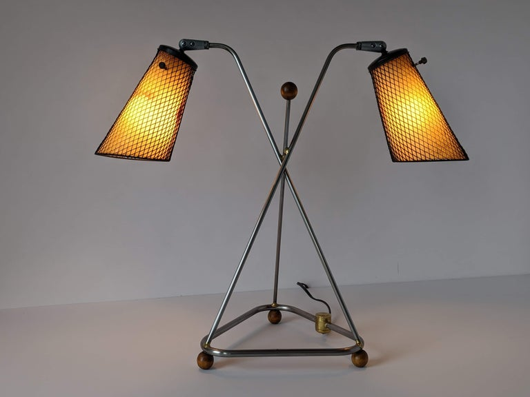 Rare table lamp designed and fabricated by Frederick Weinberg with characteristic steel mesh and fiberglass shade.  Raw metal structure assembled with brass welding.  Well aged wood eyeball feet and accent.   Solid well made