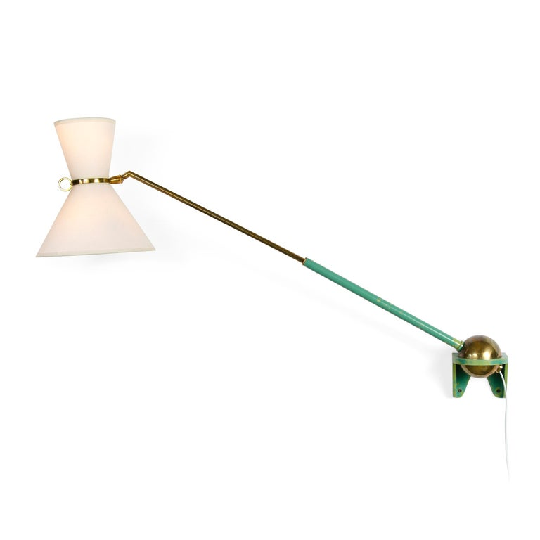 An uncommon adjustable and telescoping wall lamp with a painted steel bracket and frame with brass details.