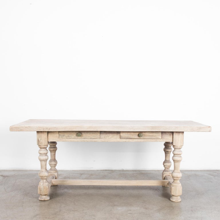 A wooden dining table from 1950s France, made of bleached oak. Sturdy turned table legs support a broad tabletop. A square apron hosts two small drawers. With the robust proportions of countryside practicality, a bright bleached oak finish gives