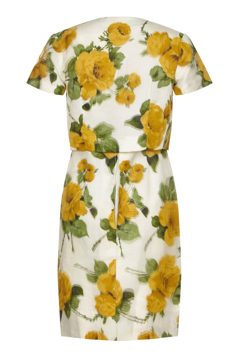 This stylish 1950s silk organza floral print dress exudes the smart city glamour of the era. The large floral print in golden yellow, green and soft cream is printed on the silk organza overlay as well as the underlay of the garment so that the