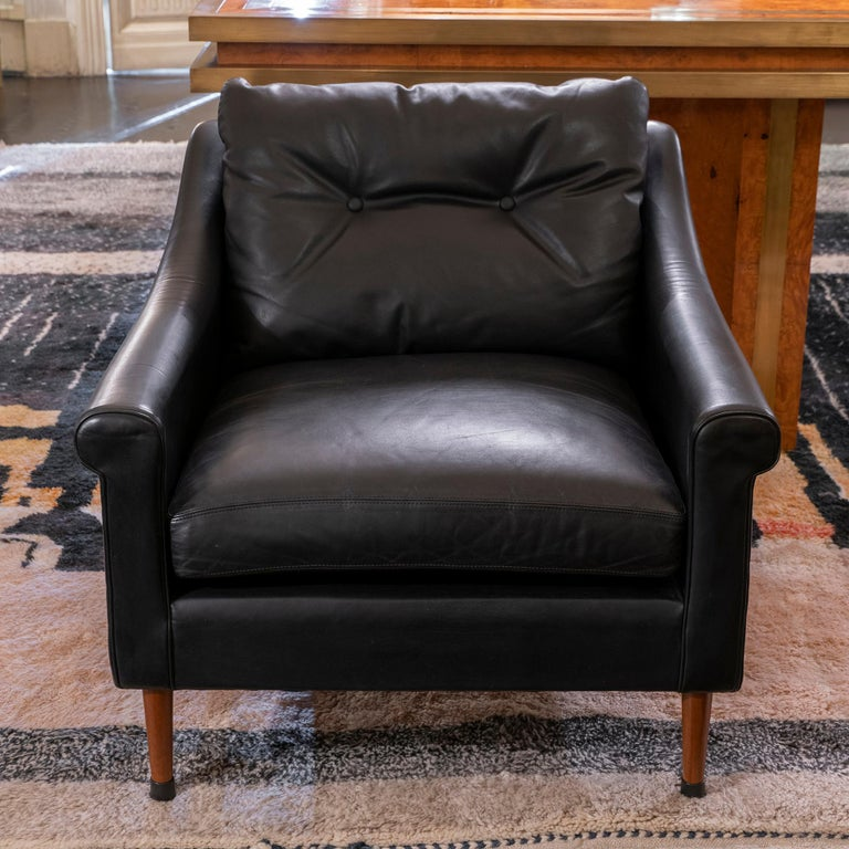 Pair of Mid-Century Modern armchairs, original black leather in perfect condition and vintage patina. Wood legs with original rubber caps, France, circa 1950s.
