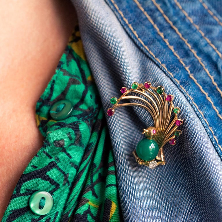 Brooch in 18 karat yellow gold, eagle's head hallmark. Lovely retro brooch, it represents a bird of paradise, the feathers being set with alternating rubies and emeralds, the belly a chrysoprase pearl, the eye, a cabochon ruby. The bird is placed on
