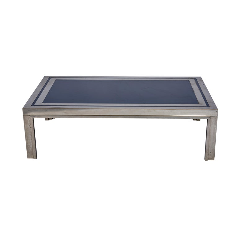 This Midcentury French steel with navy enamel top coffee table is chic and substantial.  Since Schumacher was founded in 1889, our family-owned company has been synonymous with style, taste, and innovation. A passion for luxury and an unwavering