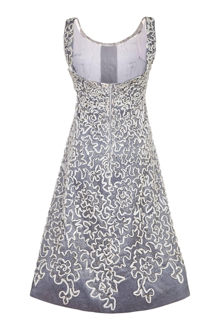 This beautiful vintage 1950s dress showcases some incredible embellishment detail with ivory tulle appliqué ribbon work on a silver/grey tulle base featuring scattered bugle beads and prong set crystal rhinestones.  This intricate abstract floral