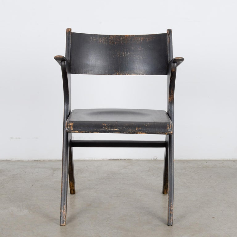 A wooden armchair with a folding seat from France, circa 1950. Upraised armrests encourage a studious, attentive position. The lively curve of the legs, out-splayed, nipped at the waist, provides a playful counterbalance. A scuffed patina brindles