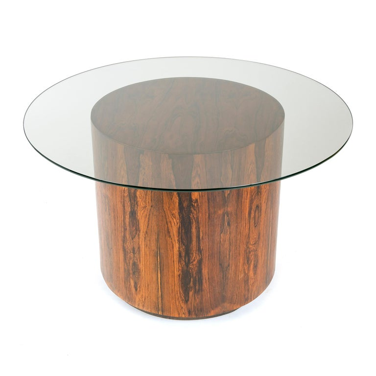 A thick, glass-topped game or dining table with a round veneered base in the style of Milo Baughman.