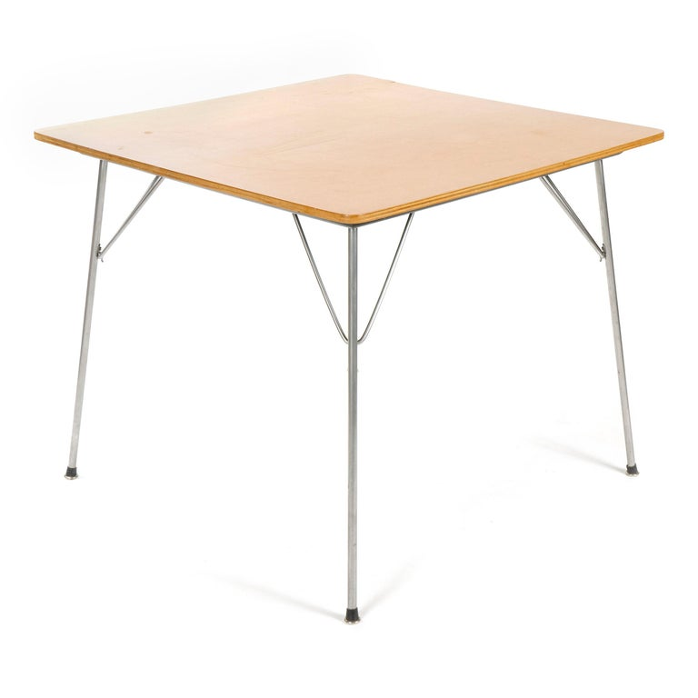 A square dining or game table with an ash top, on folding steel legs. Model DTM.