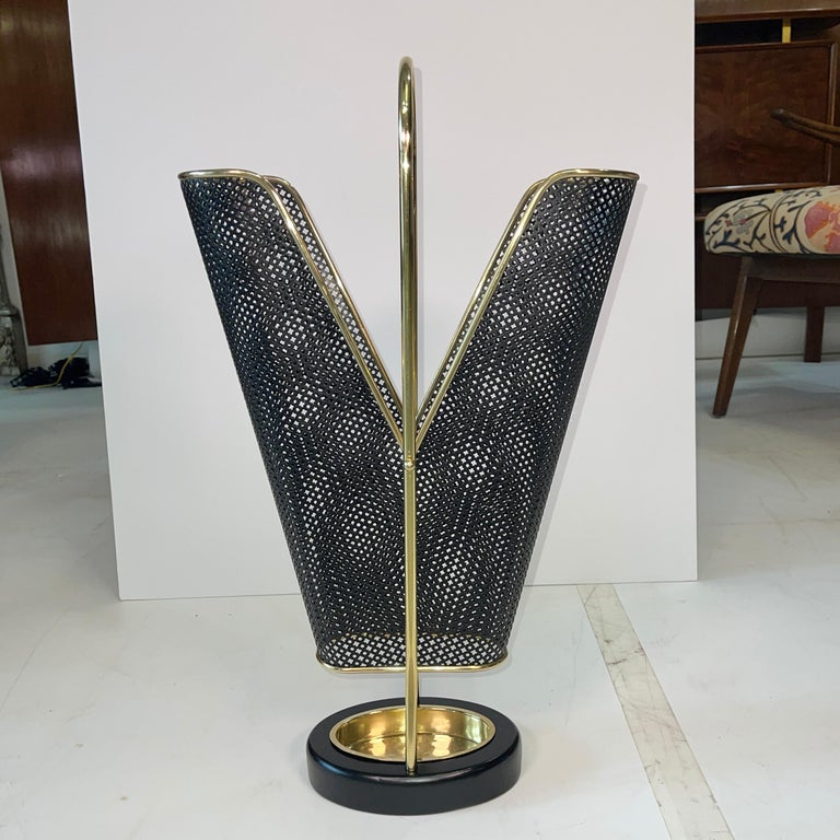 1950's German umbrella stand in brass and black enemaled perforated metal produced by Vereinigte Werkstätten München (United Workshop for Arts and Crafts). Very well constructed as well as seriously chic. The cast iron oval donut hole base is