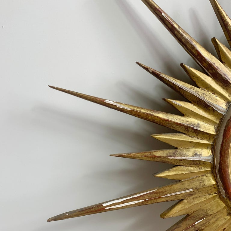 1950'S gilt convex sunburst mirror, French Wooden sunburst mirror with gesso and gilt overlay Measures: 66 cm width, 3.5 cm depth Convex glass mirror Some losses to gilt with age and use as expected No damage to spikes Small hook on the