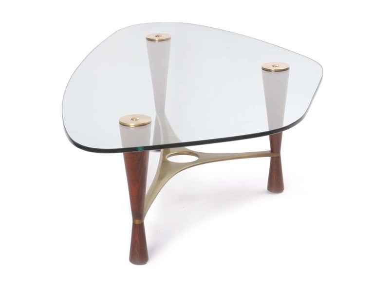 The Classic Dunbar 5309 cocktail table with shaped glass top, cast and machined brass stretcher with turned solid rosewood legs designed by Edward Wormley and made by Dunbar, Berne Indiana, 1953.