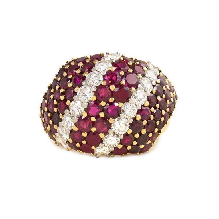 A ruby and diamond bombé ring, the rubies and diamonds set in a diagonal pattern, in 18k gold with pierced gallery.  Atw 7.50 cts. rubies, atw 2.00 cts. diamonds.  Top of ring measures approximately 3/4 inch x 1 1/16 inch
