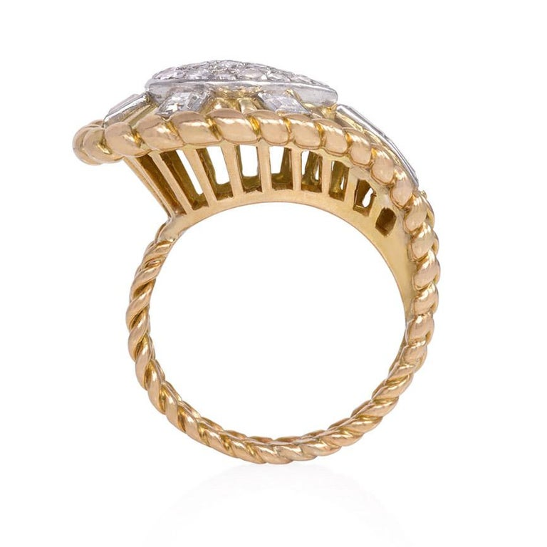 A diamond cocktail ring of tapering and radiating teardrop design with a rope twist border and raised gallery, in 18k gold and platinum.  French import marks.  Atw 1.12 cts.  Top approximately 20mm high Current ring size: US 6 1/2 (Please contact us