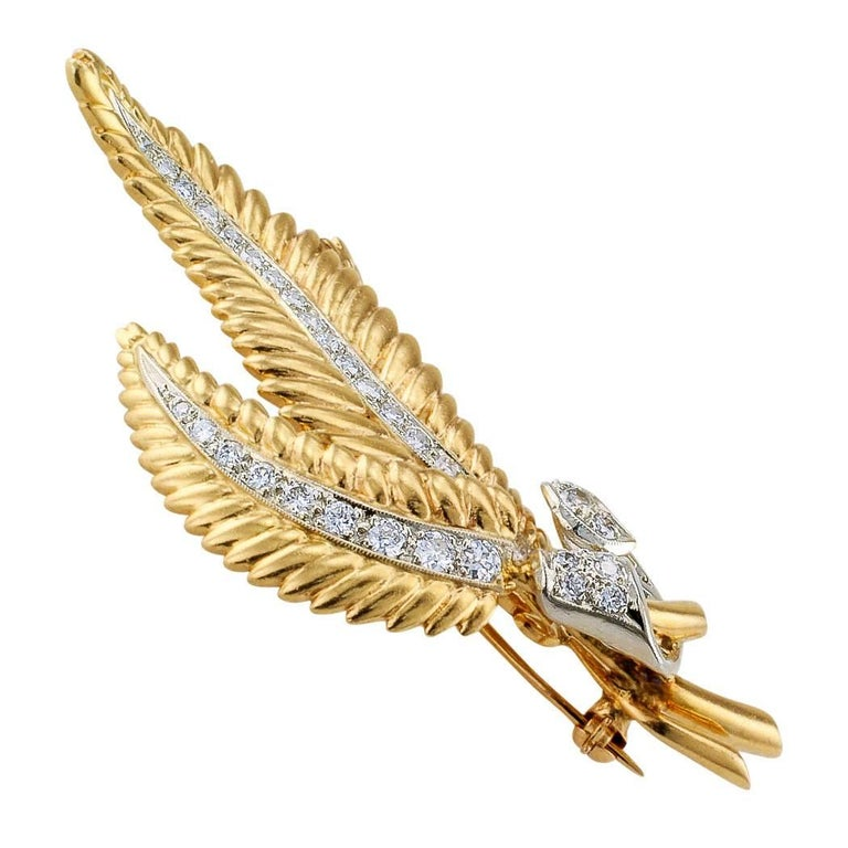 Mid-century diamond and gold fern frond brooch circa 1950. Designed as a graceful trio of diamond-set fern fronds gathered at their bases by an unfurling ribbon of diamonds, the diamonds totaling approximately 1.50 carat, approximately H color and