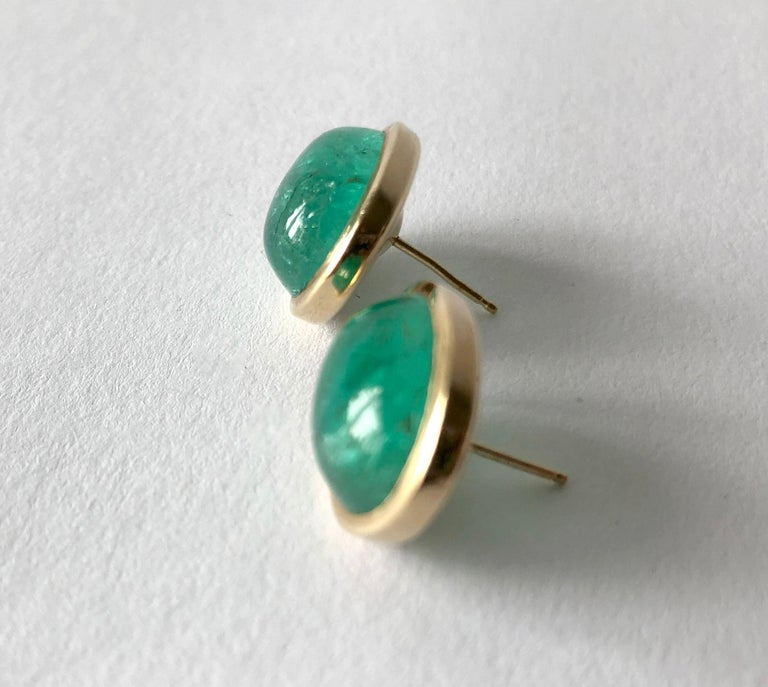 Pair of oval emerald earrings set in gold, circa 1950's.  Earrings are rich in color with natural inclusions. The emeralds are approximately 9 ct each.  The overall measurement of the earrings are 3/4