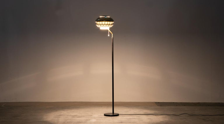 Brass floor lamp, black leather stem by Alvar Aalto, Finland, 1953.  This magnificent floor lamp is designed by the famous Finnish architect Alvar Aalto. The lamp comes with an enthusiastic lampshade in brass and contains white metal, the lamp