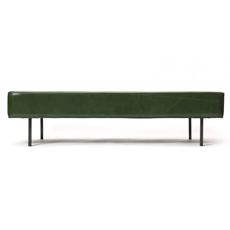 A large daybed or bench on four square black steel legs in the original green leather upholstery. Made by H G Knoll.